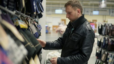 Young caucasian man choosing slippers at the supermarket. Selecting comfortable homewear