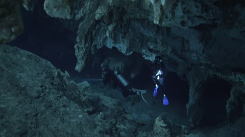 two divers underwater with flashlight swimming through stalagmite in cenote cave dos ojos
