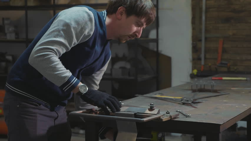 Blacksmith working with metal decorative detail at his workshop, slow motion. Men making decorate element in star shape. | Shutterstock HD Video #34312909