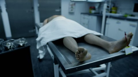The lifeless naked corpse of a young mixed race male is laid out on an autopsy table, all alone and with a tag on the toe.