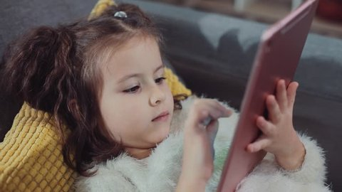 Close up serious cute little girl sitting at table using tablet computer looking seriously thinking pc people education internet online technology play beautiful caucasian child childhood slow motion