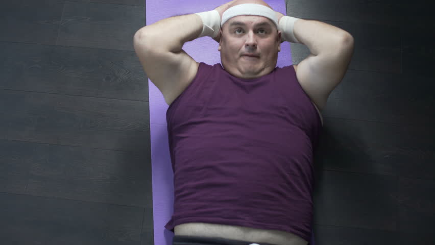 Obese person in sportswear doing crunches on floor mat at home, lazy workout | Shutterstock HD Video #34350829