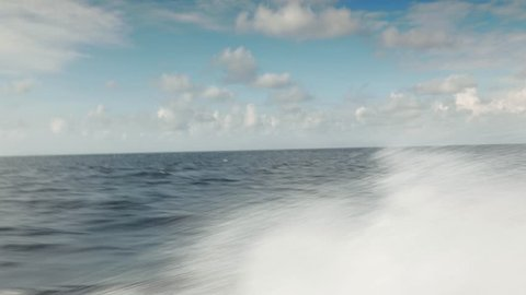 Speed boat travelling bow wave splashing water pacific ocean horizon Indonesia July 2017
