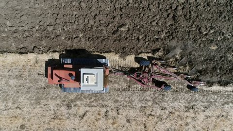 Aerial top-down view of tractor on continuous tracks plowing the brown landscape preparing the soil for planting crops because of steep uphill route these tank tracks or caterpillar tracks are needed