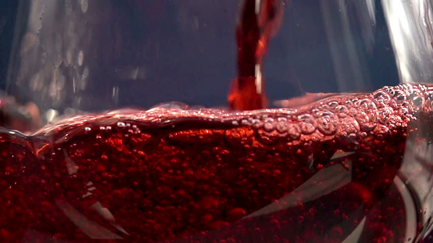 Pouring red wine. Slow Motion at a rate of 480 fps. Red Wine is poured into the glass on a blue background