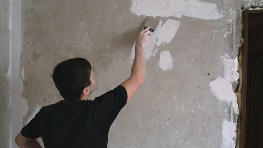 Man cleans the spatula pieces of wallpaper from beton wall