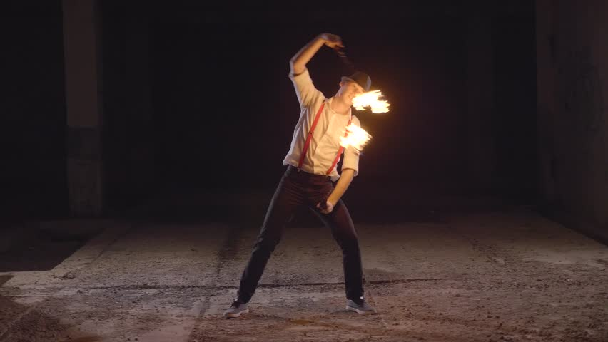 Male artist performing fire show at dark abandoned building in slow motion. Fireshow in ruins at night.