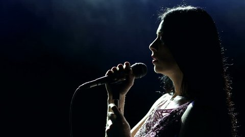 Portrait of a beautiful singer with long hair on a dark smoky stage in the spotlight. Female singer on the stage holding a microphone.