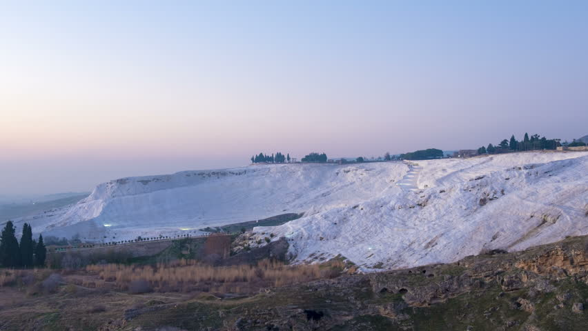 Zoom out time lapse view of white calcium carbonate travertine absorbing colorful evening sunset, dusk colors in day to night transition at Pamukkale, Turkey. 4k 24fps