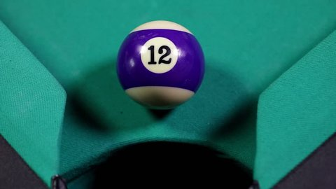 Close up of a snooker ball number 12 with purple color get into billiard pocket