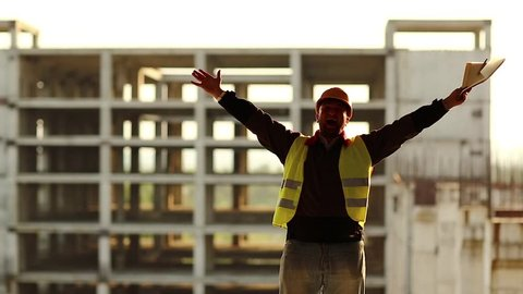 Happy builder on construction site. Merry workman with work papers on construction site, builder with documentation in hand celebrates victory and finishes work, hands up