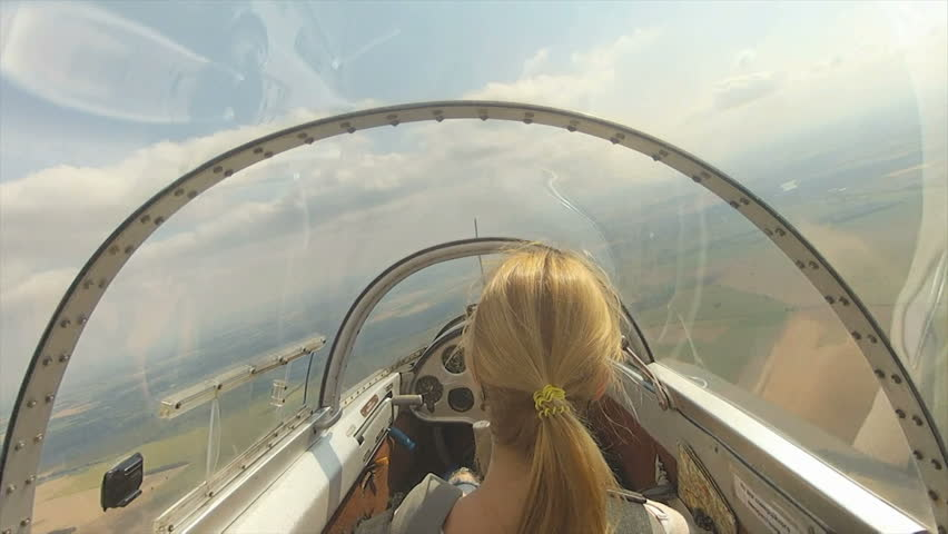 The glider flying. Woman in cabin of the glider.