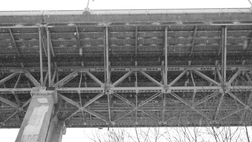 Underneath Leaside bridge in the Don Valley, Toronto, Canada. Snow falling. Winter. Handheld shot with stabilized camera. Black and white.