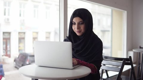 Attractive woman in hijab searching for something in internet. Portrait of smiling young muslim woman working on modern laptop in cafe. Studying or working. Slowmotion shot