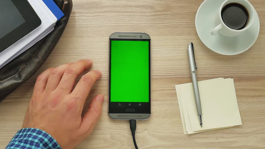 Man using a modern smartphone with green screen at her desk - green screen for placement of your own content | Shutterstock HD Video #34498939