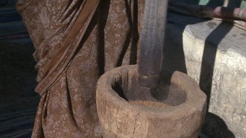 Indian woman grinding seeds in a wood mortar outside