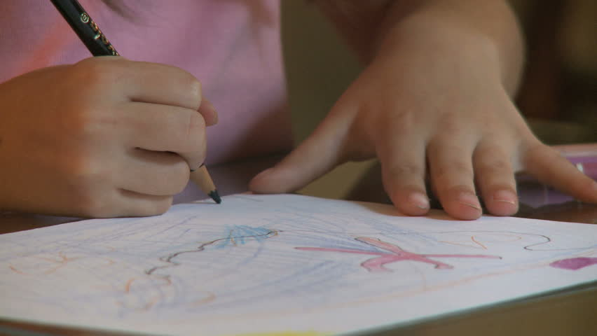 Close up of a young childs hand coloring.