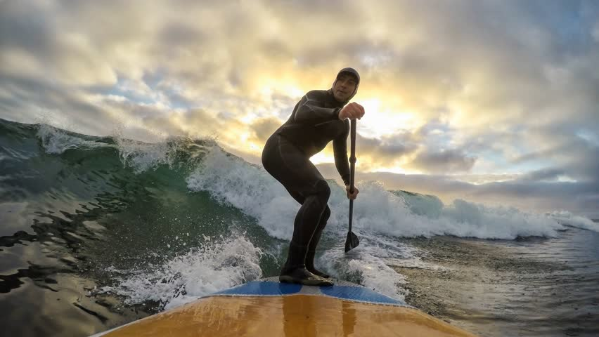 Cinemagraph of a man surfing a wave on a stand-up paddle board during a vibrant sunset. Taken in Tofino, Vancouver Island, British Columbia, Canada. Still image animation