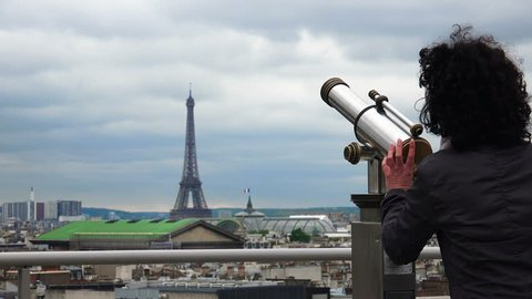 Tourist, Girl looks in Binoculars in Paris with view of Eiffel tower at background