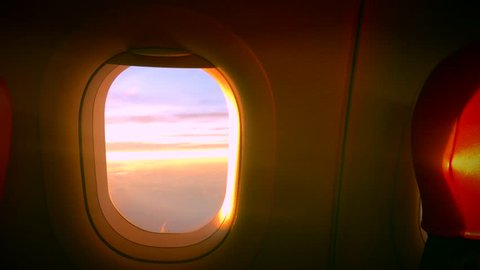 Cloud Window seat airplane concept. Sky cloud view from Seat airplane close up window on sunset beautiful. It sky blue or azure sky and cloud over land in daytime beauty. This window behind red seat