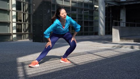 full length of Young fitness woman stretching and warm up before starting to run
