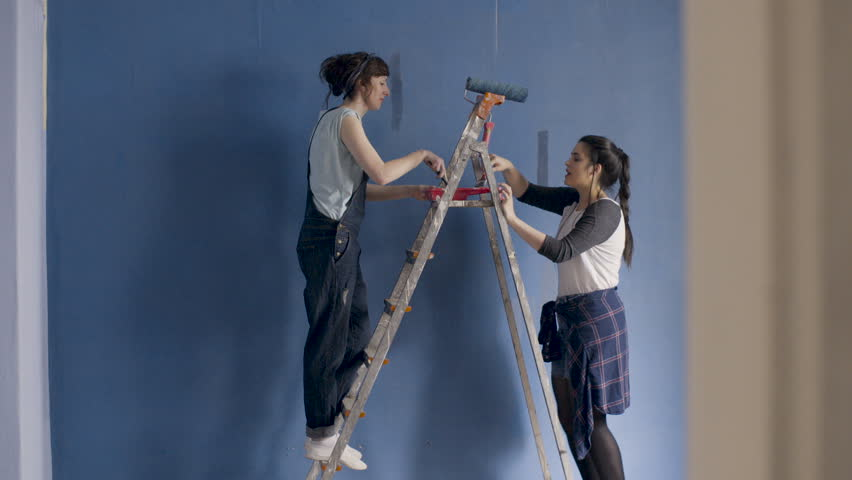 Two funny girlfriends dance sing and paint a walls at home in blue with the help of paintbrushes.    | Shutterstock HD Video #34594399