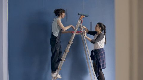 Two funny girlfriends dance sing and paint a walls at home in blue with the help of paintbrushes.