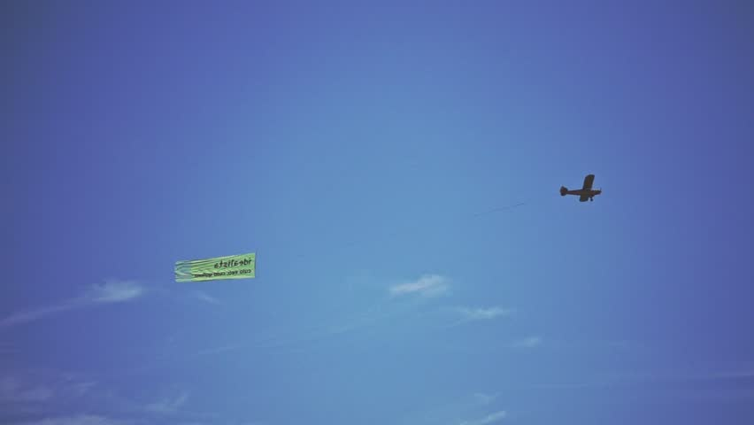 Single engine plane flying in the air. Bottom view of small airplane flying through blue sky and towing advertisment banner. Aerial advertising concept