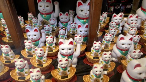 beckoning cat figurines in a store window of chinatown in san francisco, usa