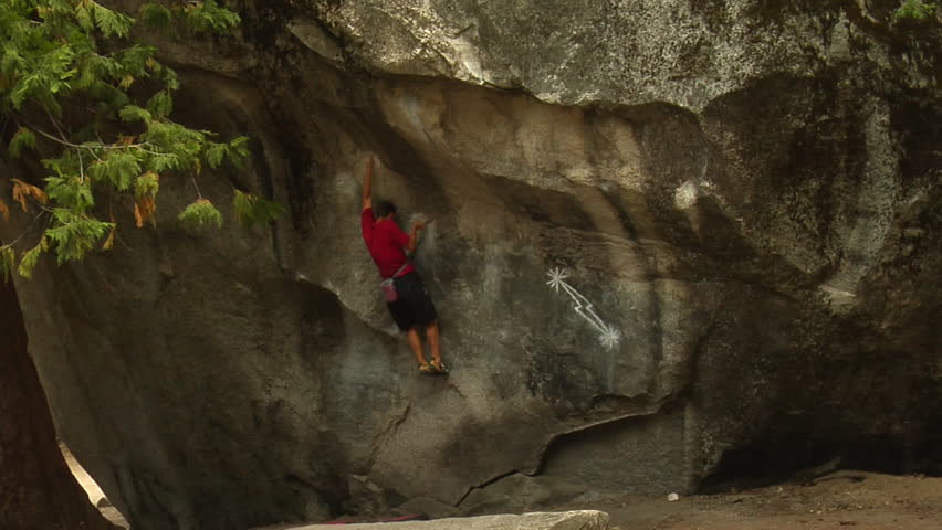 A mountain climber climbs up a rock face with no safety gear by himself during the day in Yosemite national park