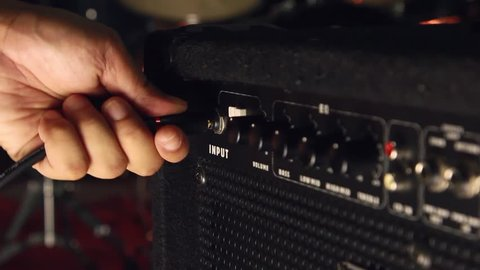 A man is holding electric bass and plugging in jack bass into bass amplifier.