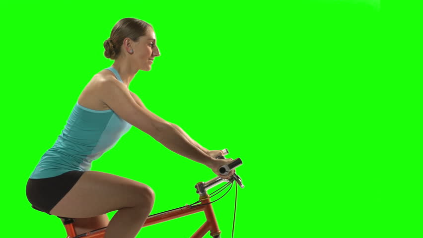 Young Woman doing a fitness routine on bike in front of Green Screen, profile #3463109