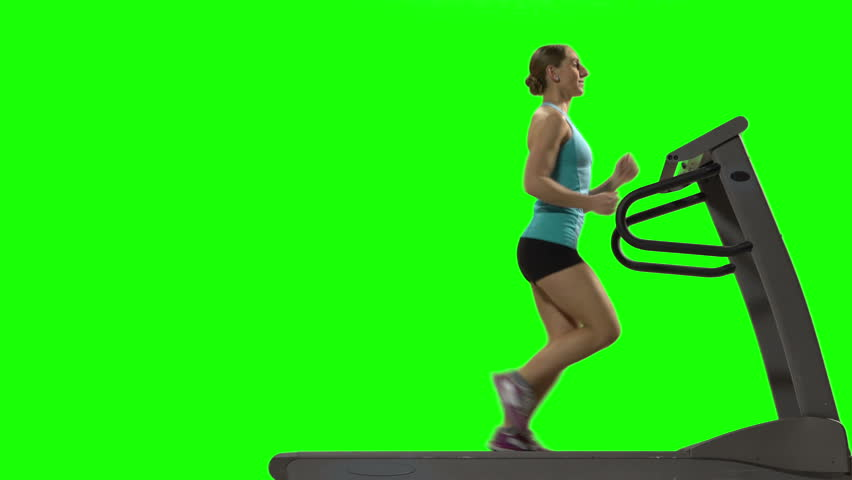 Young woman running on the treadmill in front of green screen, profile