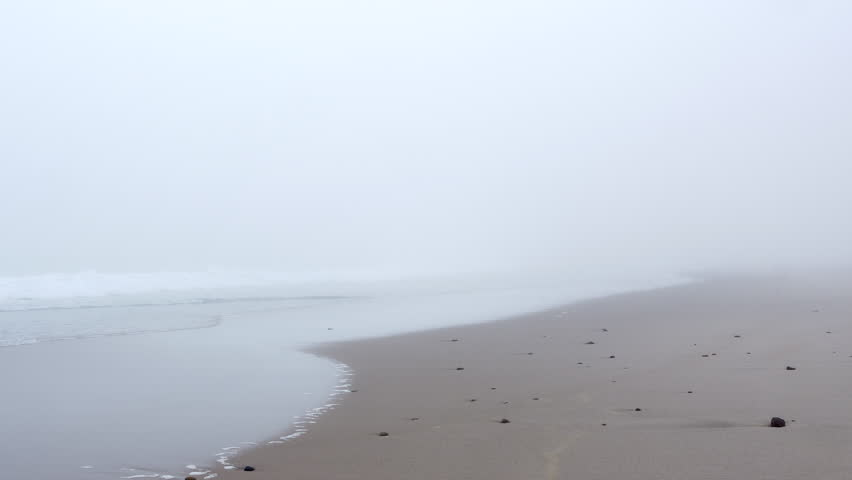 Waves slowly and calmly rolling over sandy foggy beach at the ocean on Cape Cod.