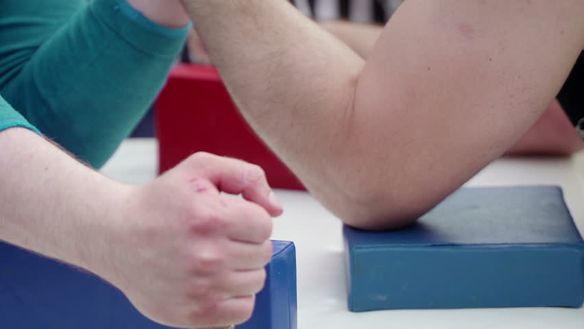 Two unrecognizable men arm wrestling. Concept of struggle, confrontation and heavy sport. Conflict, win and loss, winning and losing. Competition in power struggle with hands. Force, energy and will