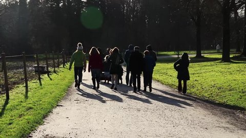 group of people going for a walk in the park in winter, beautiful sun flare