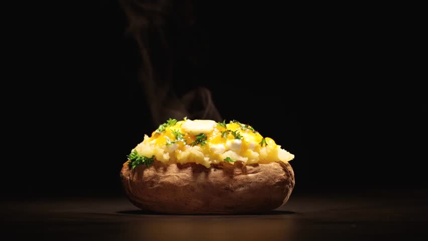 Cinemagraph - A hot loaded potato with steam garnished with parsley and butter against a black background