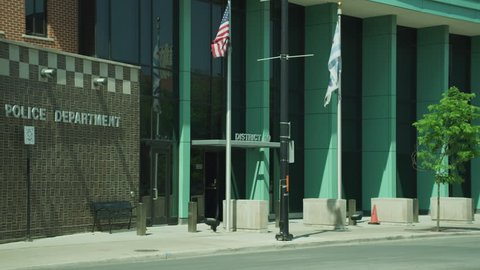 Day Raking shot Chicago police station name not visible station brick green border There an American flag visible Tilt up second story windows