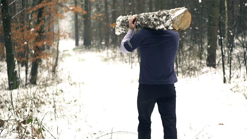 Lumberjack strong man carrying downed log, slow motion shot at 240fps, steadycam shot