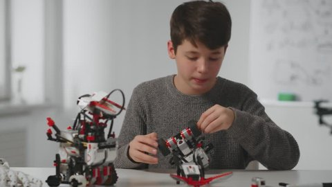 Boy teenager constructing model bot car at desktop in modern technical laboratory at classroom on background white marker board close up