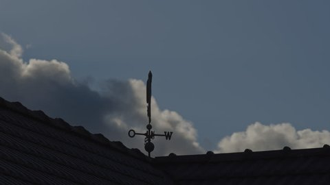 Time Lapse Of German Weather Vane Rooster On Tiled Roof Top With Heavy Clouds