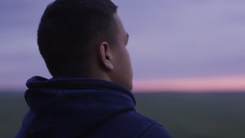 Young man is looking at the sunset thinking. Young man looks at the sunset, being alone, the concept of freedom