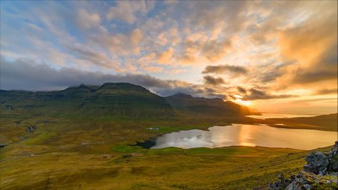 A colorful sunset fills the sky as seen from Kirkjufell, Iceland. Golden rays of sunlight are reflected in the ocean.