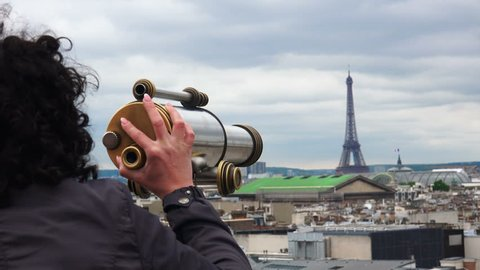 Beautiful girl looking through coin operated binocular on terrace of Laffaete Galery in Paris, France. View of Eiffel Tower and Opera Garnier at background