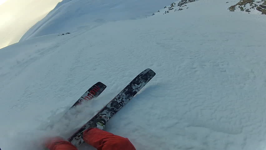 A skier carves back and forth as he rides down a mountain covered in fresh powder during the day. It is shot with a camera mounted to the athletes head and provides a POV, point of view, perspective. | Shutterstock HD Video #3474209