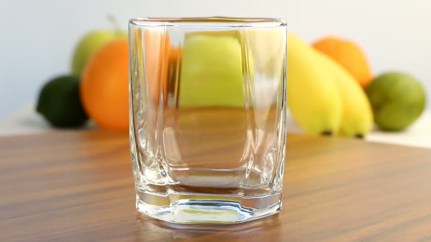 Fresh citrus fruits. Video footage of the concept of a healthy diet and diet. Orange juice is poured into a glass, with a background of different fruits: banana, lime, lemon, orange. It's spinning   Shutterstock HD Video #34747369