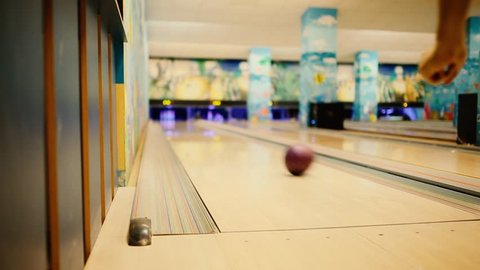 In the game club for bowling, the player throws a bowling ball that knocks down skittles. The player knocks out the strike and is happy with the victory.