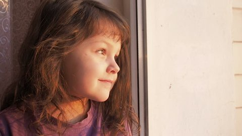 The child sits on the windowsill and looks at the sun. A little girl looks out the window.