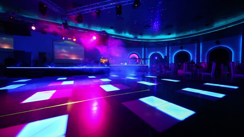 Waiter Walks In Club With Dance Floor Near Stage And Bar