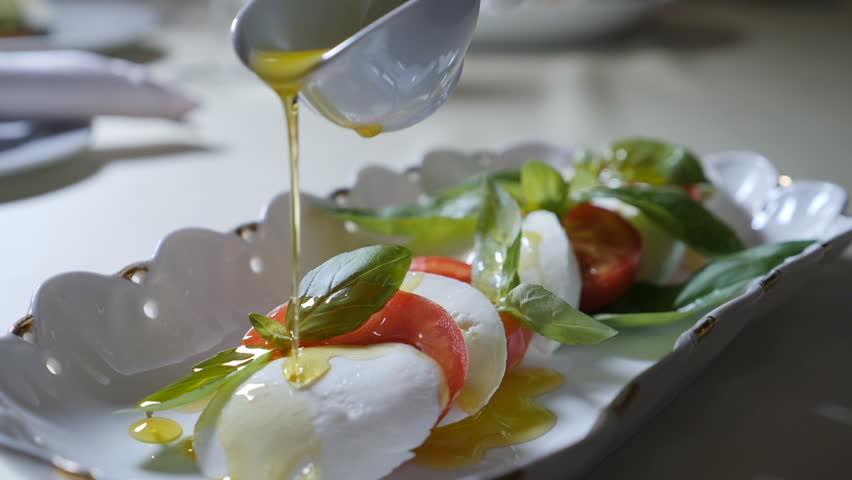 Healthy food and vegetarian concept. Close up of Pouring olive oil over caprese salad. Italian caprese salad with Mozzarella cheese. Slow motion
